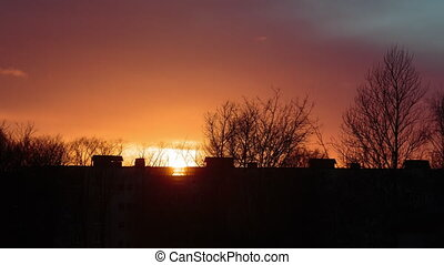 Sunset in a village behind high rise buildings. Time lapse video.