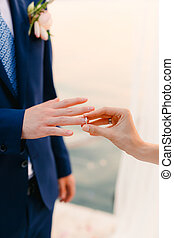 The bride puts the ring on the bridegroom at the wedding...