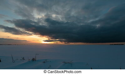 Sunset in the winter snow field. Time lapse