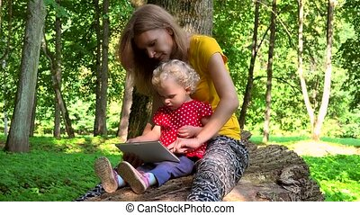 Mother with toddler daughter girl using tablet computer sit on fallen tree trunk