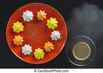Multi-colored figured cookies on a round orange plate and a...