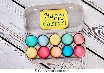 Egg tray, happy Easter card. Two rows of bright eggs....