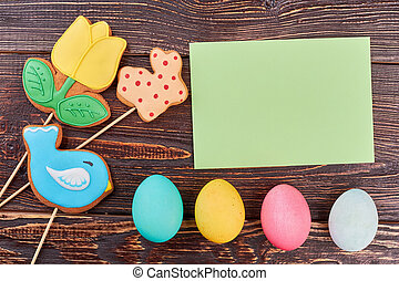 Easter eggs, blank green card. Colorful cookies on sticks....