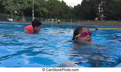 Kids enjoy the water in a swimming pool