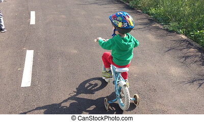 kid with helmet riding bicycles with training wheels - Shot...