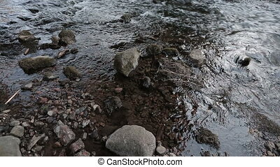 River is washing the stones with its current. Video full hd.