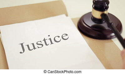 Justice folder with gavel placed on desk of judge in court -...