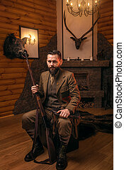Hunter man with old gun sitting on antique chest - Hunter...