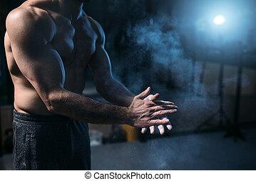 Male athlete rubs hands with talcum powder. Gymnast prepare...