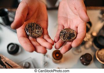 Watchmaker hands with clockwork mechanism closeup -...