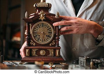 Watchmaker with old mechanical desk clock. Hour workshop