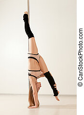 Young slim poledance woman stretching in lingerie. Beautiful...