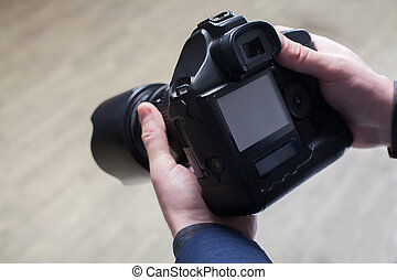 Male photographer hands holding digital camera
