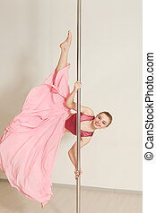 Poledance woman stretching in beautiful pink dress - Young...