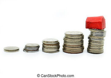 Coins stacked up in piles with color house. Saving for home...