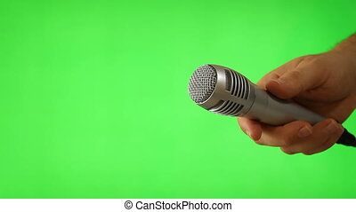 Holding Up The Mic Isolated On Green Screen - Shot of...