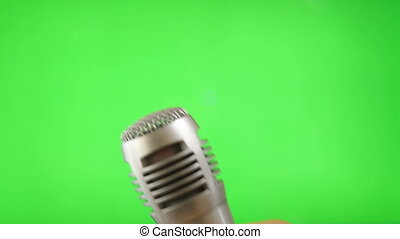 Holding Microphone Isolated On Green Screen - Shot of...