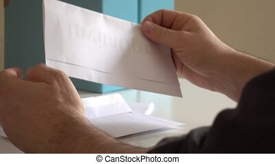 Hands of man opening an invitation letter - opening an...