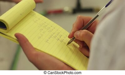 Hand writes on a yellow block pad - Shot of Hand writes on a...
