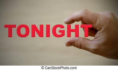 Hand holding the word TONIGHT - Shot of Hand holding the...