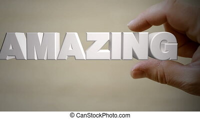 Hand holding the word AMAZING - Shot of Hand holding the...
