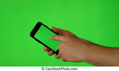 Hand holding mobile phone with green screen