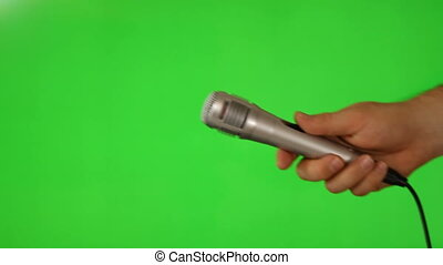 Hand hold a microphone on green screen