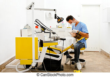 Dentist chair - Dentist and female patient at dental office...