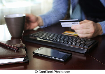 man pays for online purchases with a credit card