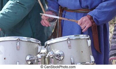Man Playing the drum - A man is playing on a big shabby drum