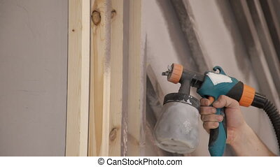 close-up of worker hand using spray gun and painting wood in...