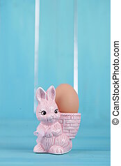 colorful egg cups with easter bunny on blue background