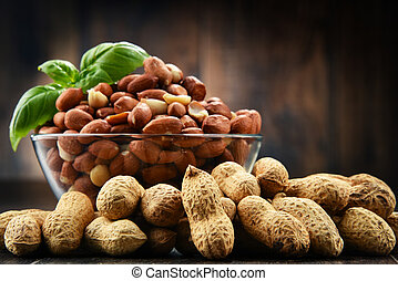 Bowl with peanuts on wooden table.