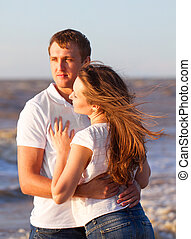 Attractive happy young couple cuddling at the beach.