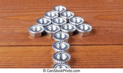 Nuts for bolts lie on a wooden table in the form of an...