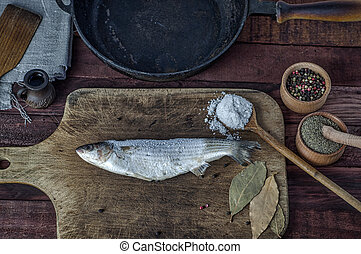 Frozen fish smelt on a kitchen cutting board, near a spice...