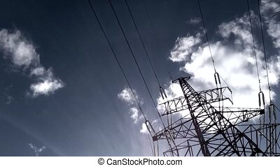 Moving clouds in the sky, wires and high-voltage tower. Timelapse