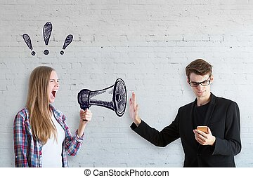 Woman with megaphone, man with phone - Young woman with...