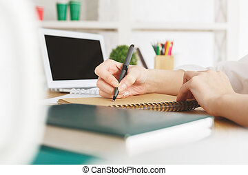 Female with laptop writing in notepad - Close up of female...