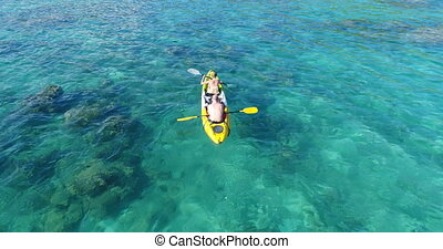 Aerial shot of couple kayaking in turquoise sea during...
