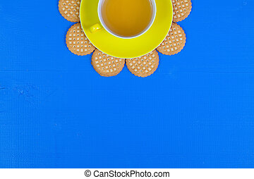 Funny arrangement cup of tea on blue wooden table with sweet...