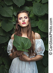Woman with makeup in nature. - Portrait of a young woman...