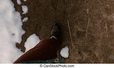 Man walks along the sand in early spring when all the snow has not melted yet. First person view.