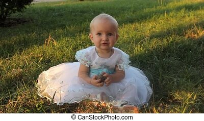 A baby girl sitting on the grass in a white dress and holding a fir-cone. Sunset in summer.