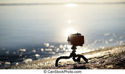 Action camera on gorilla tripod on embankment - Action...