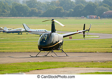 R22 helicopter - Black R22 helicopter standing on the...