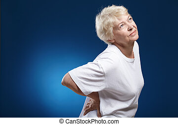Back ache - An elderly woman with a sick back on a blue...