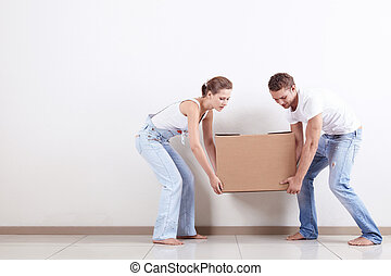 The couple moved - Young couple gently drags a box