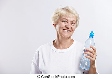 Healthy lifestyle - An elderly woman with a bottle of...
