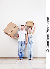 Removal - A young couple holds boxes in apartment